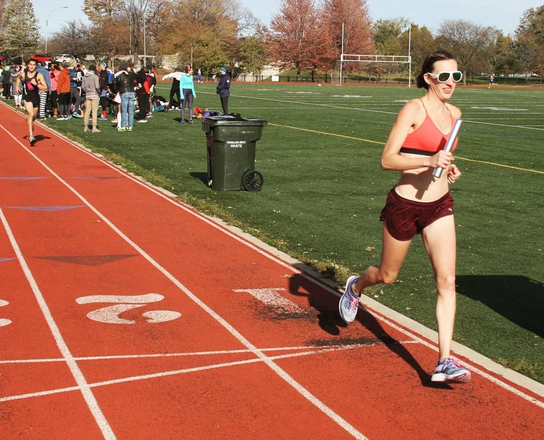 Author running a mile relay on the track in a sports bra and shorts.