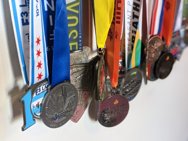 Race medals hanging on a wall.